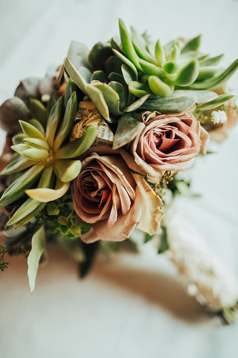 Close up photo of bride bouquet of mauve amnesia roses, paper flowers and succulents