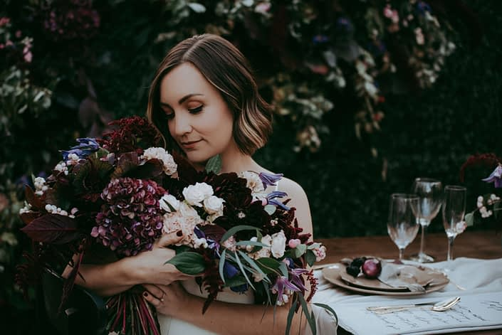 Bride holding bridal bouquet designed with burgundy hydrangea, clematis and blush spray roses with boxwood backdrop