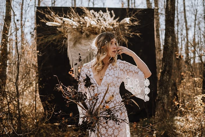 Fall boho bride with lace dress in the wood with dried pampas grass hanging with crochet and twig and a boho floral headdress