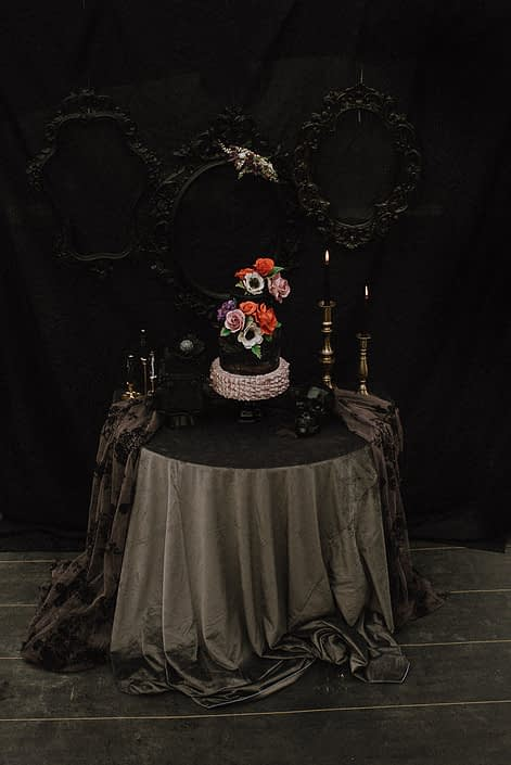 black backdrop for wedding cake with grey tablecloth and sugar flowers with red roses and mauve roses and white anemone
