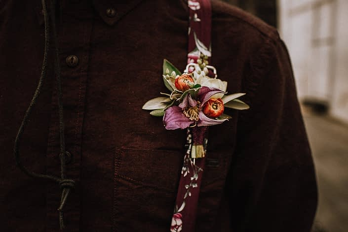 alternative groom in floral suspenders with boutonniere with red ranunculus buds and purple clematis