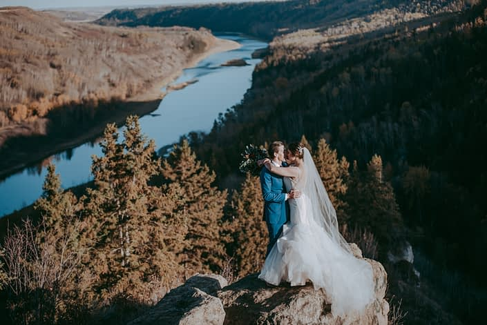 Beautiful river valley view wedding photo of bride and groom in fall with long veil and groom in a blue suit