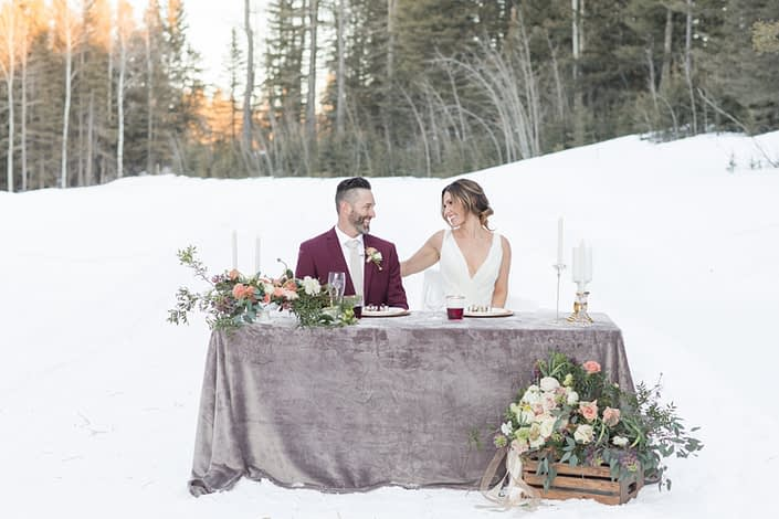 Winter wedding with bride and groom in burgundy suit Flowers in white, ivory and peach