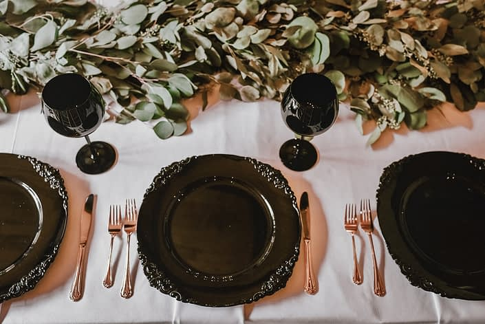 Wedding table setting with a white linen, black wine glasses and charger plates, gold cutlery and eucalyptus garland runner