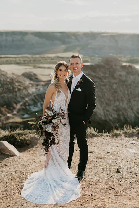 bride and groom at a styled photoshoot in the drumheller badlands with a lace dress and a loose organic bridal bouquet