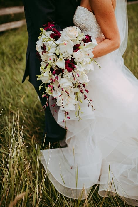 Bride holding a cascade bouquet designed with white cymbidiu orchids and dendrobium orchids and white calla lilies and roses