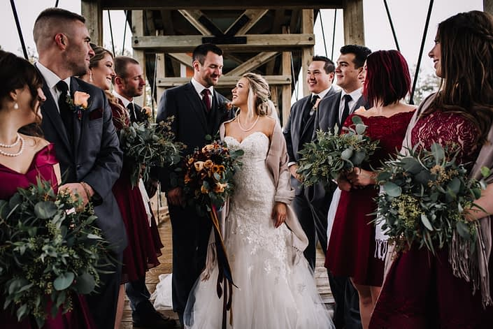 Wedding party with bride, groom bresmaids and groomsmen standing on a rustic bridge holding eucalyptus grenery bouquets and bridal bouquet in autumn colors