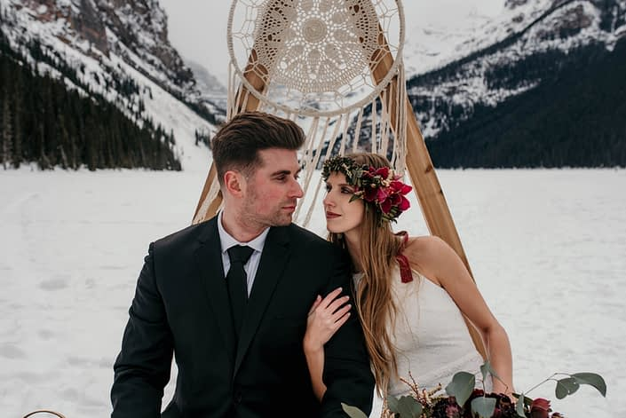 bride and groom with a floral crown in boho winter photoshoot at lake louise