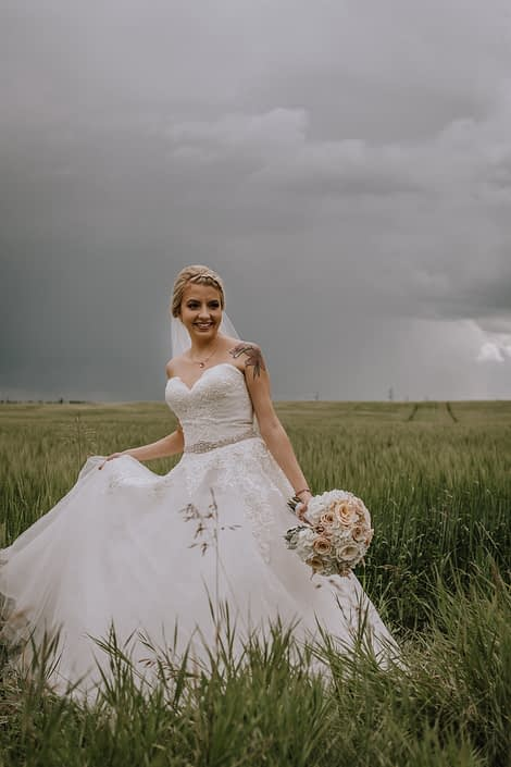 bride in a summer wheat field in alberta holding a bridal bouquet of blush roses and white hydrangea and dusty miller