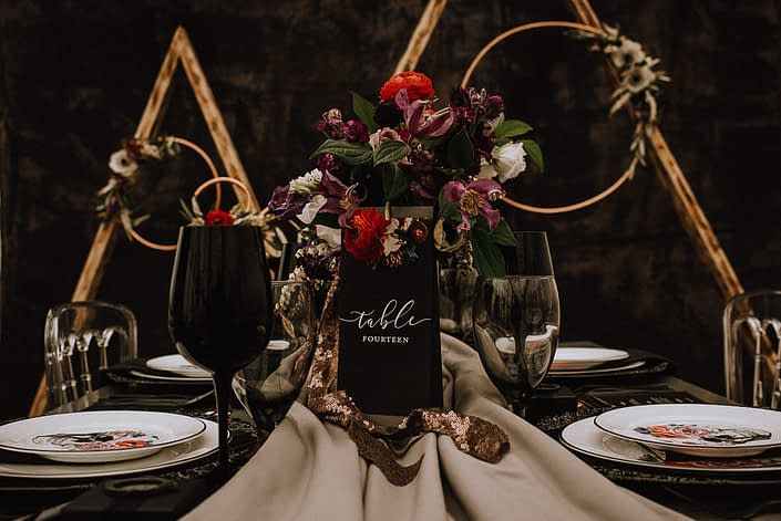 alternative bridal table setting with red ranunculus and purple clematis and white lisianthis and copper floral hoops and triangle archway