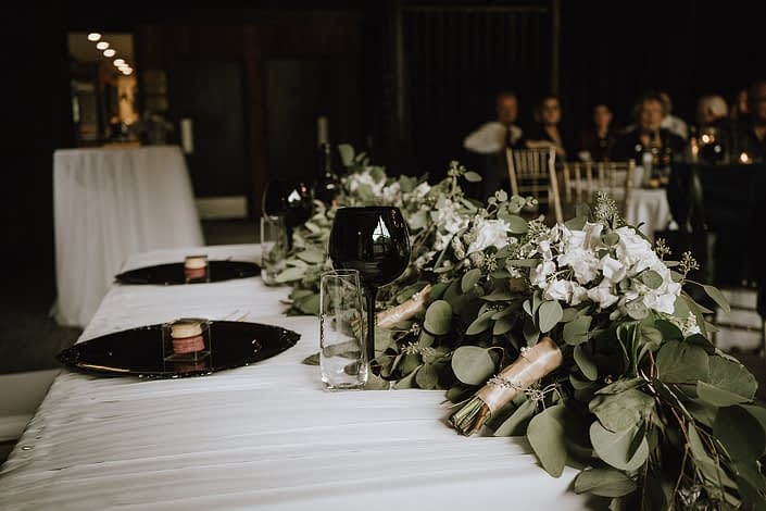 sweetheart table with bridesmaid bouquets and eucalyptus garland and black charger plated and wine glasses