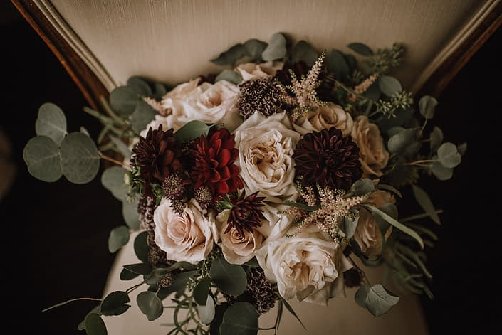 close up of bridal bouquet on antique ivory chair designed with plum scabiosa, burgundy dahlia, white ohara garden roses, quicksand roses, burgundy astrantia and pale pink astilbe