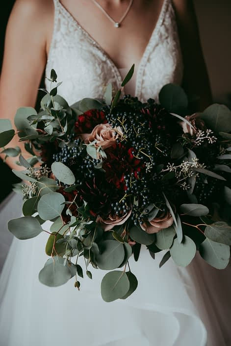 bridal bouquet close up with red roses burgundy dahlias amnesia roses navy viburnum berries and mixed eucalyptus