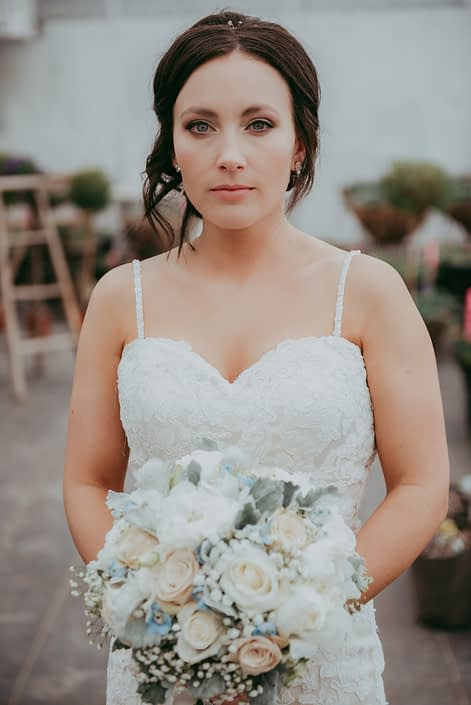 bride holding a bridal bouquet of ivory rose, white peony and pale blue delphinium