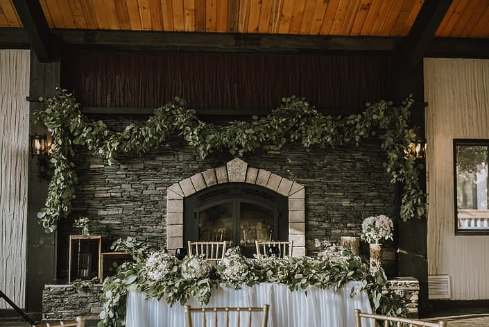 wedding sweetheart table at Canyon Ski resort in red deer alberta with fresh eucalyptus garland on mantle and along the front of the head table