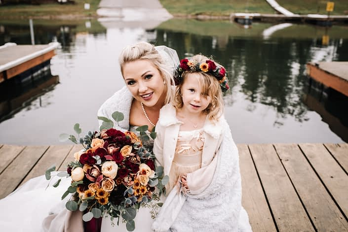 Bride with a bridal bouquet designed with burgundy roses, peach garned roses, burnt orange chrysanthemum and eucalyptus with a flowergirl wearing a flowercrown of red spray roses and chrysanthemum