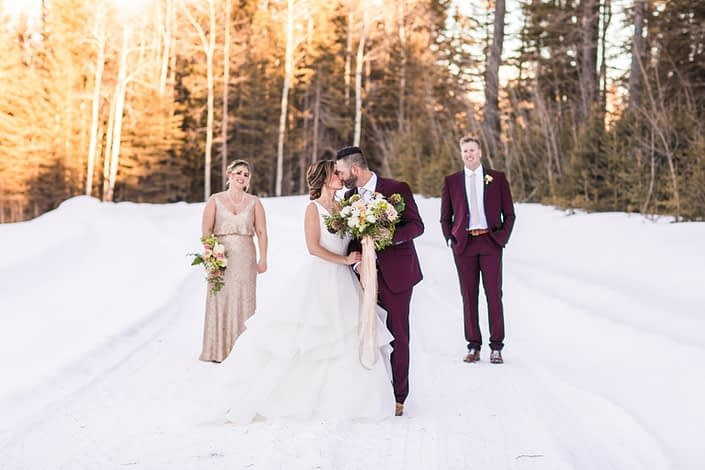 Winter wedding party with bride, bridesmaid, groom and groomsmen in Burgundy suits and blush sequin dress with bridal bouquet of burgundy helleborus, blush ranunculus, heleborus and white ranunculus
