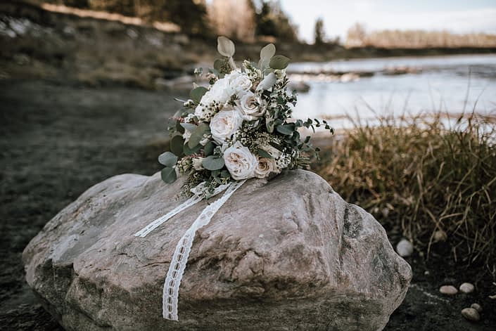 Bride's bouquet on a rock in the fall designed with white and blush roses and eucalyptus