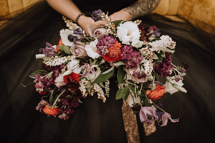 alternative bridal bouquet with black wedding dress and bouquet with red ranunculus and purple stock and white lisianthus and purple clematis and plum scabiosa and amnesia roses and a copper sequin wrap