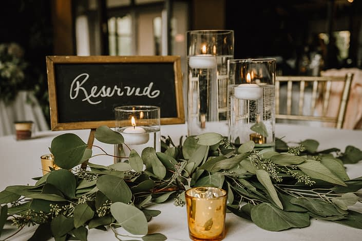 Canyon ski resort centerpiece with clear cylender vases with florating candles and eucalyptus greenery and gold gold votives
