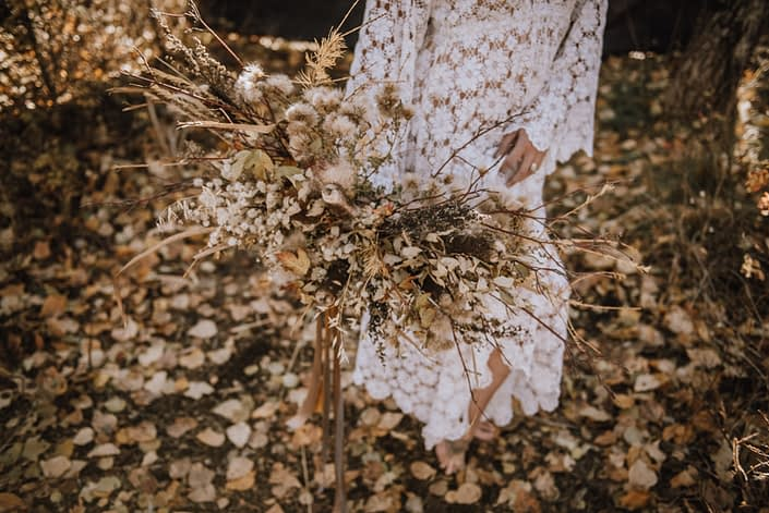 close up shot of boho bridal bouquet with fall foraged foliage and flowers in the fall in the woods bride is wearing a crocheted dress