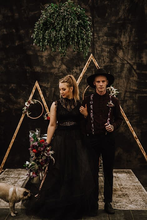 alternative wedding photo with black bridal dress and groom in black with suspenders and wide brim hat with triange arch backdrop and bouquets with red and burgundy and floral hoops and area rugs and pugs