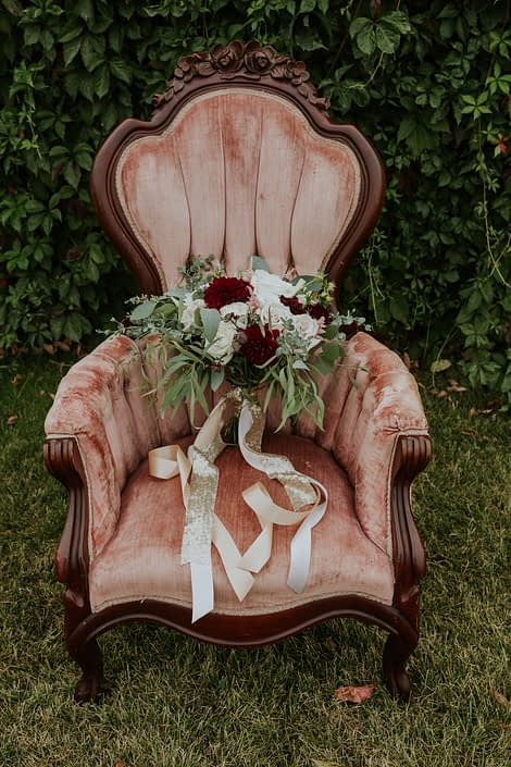 antique dusty rose chair with bridal bouquet that has trailing gild sequin and blush silk ribbons designed with burgundy dahlia, blush and ivory roses