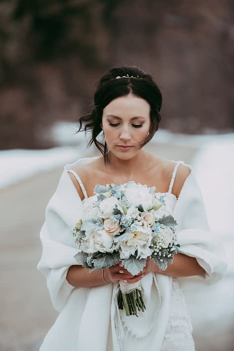 Winter bride with compact hand tied bouquet of white peony, ivory roses and delphinium