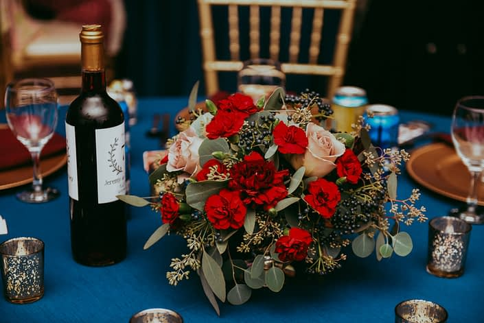 Low Centerpiece with red carnations quicksand roses and viburnum berries and mixed eucalyptus greenery on blue tablecloth with gold chairs close up shot