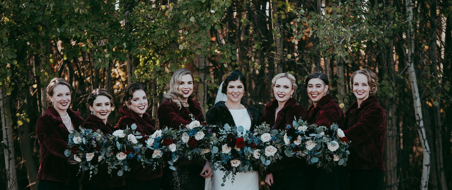 bride and bridesmaids photo with fur coats against a treed background smiling holding out matching bouquets with mixed eucalyptus greenery and red and blush roses large bridal party