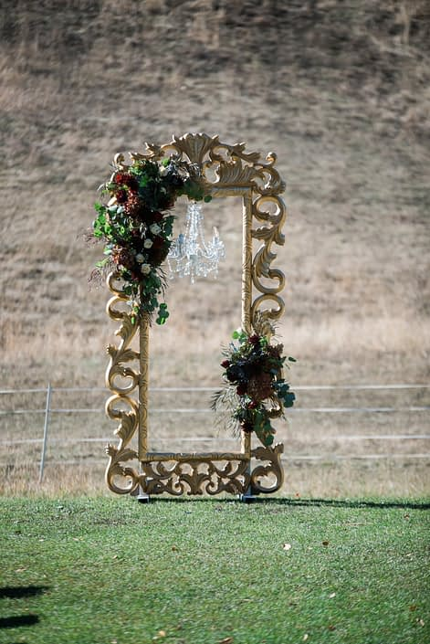Gold filagree oversized picture frame with chandelier accented by floral arrangements in burgundy and navy