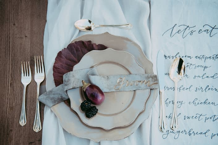 place setting on autumn harvest table with beige dinnerware and gold cutlery and velvet placecard nd burgundy floral accents