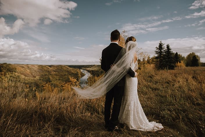 Bride and Groom with veil overlook the top of the hill at Canyon Ski Resort
