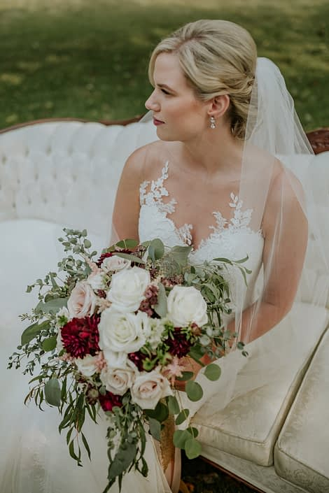 bride with a bridal bouquet designed with eucalyptus and blush and ivory roses and burgundy dahlia wearing pearl earings and an ivory veil