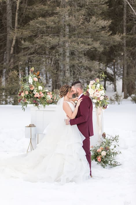 Bride and groom in winter wedding styled shoot in front of white mantle with flower arrangements in peach, blush and ivory