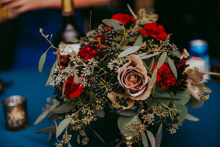 close up of low centerpiece with navy viburnum berry red carnations burgundy dahlias amnesia roses and mixed eucalyptus greenery in a compote vase on a blue tablecloth