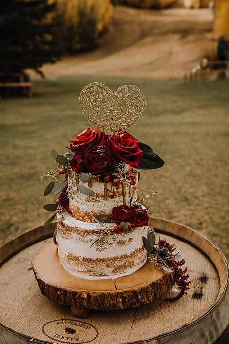Naked wedding cake sitting atop a rustic whiskey barrel accented by burgundy and red roses, hypericum berries and eucalyptus