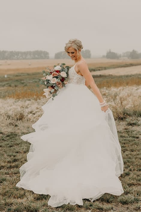 bride with flowy dress in a fall prairie field holding a bouquet with red roses and quicksand roses and white o'hara garden roses and pink astilbe and blue eryngium and eucalyptus