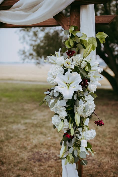 close up photo of archway arrangment with white hydrangea and white lilies and burgundy dahlia