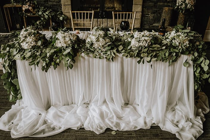 sweetheart table covered with tulle ballerina skirt linens and accented by a eucalyptus garland and white hydrangea