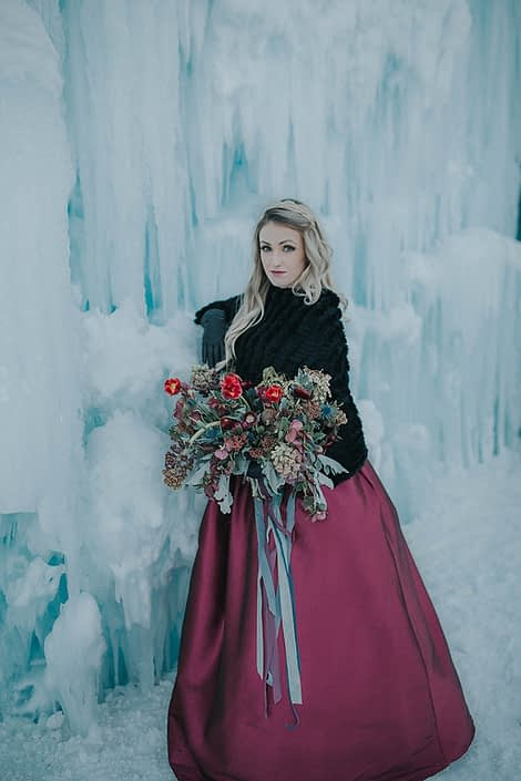 Engagement photo at the ice castles with bride bouquet of tulip frittilaria and skimmia in burgundy and red with trailing silk ribbons in grey