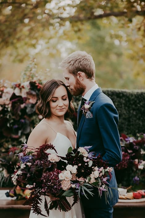 Bride holding bouquet desinged with burgundy hydrangea and amaranthus and dahlia, blush carnations and spray roses and groom with boutonniere