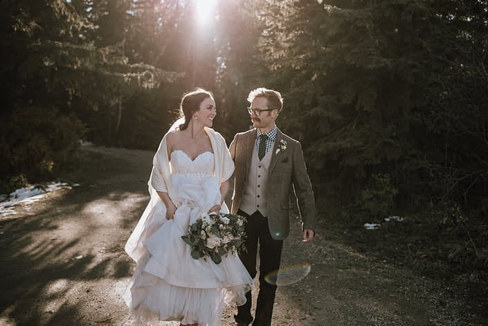 Bride in blush dress with shawl with groom in tweed at a fall wedding with a white bouquet with eucalyptus