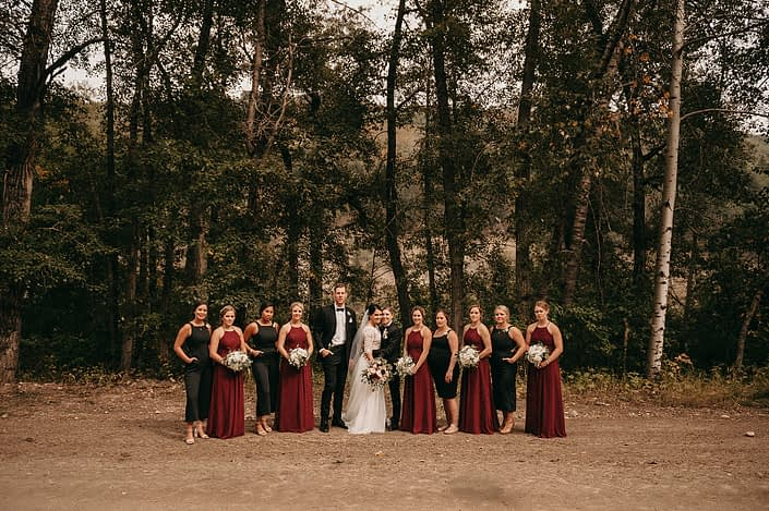 wedding party with bridesmaids in black jumpsuits and burgundy long dresses with white hydrangea bouquets