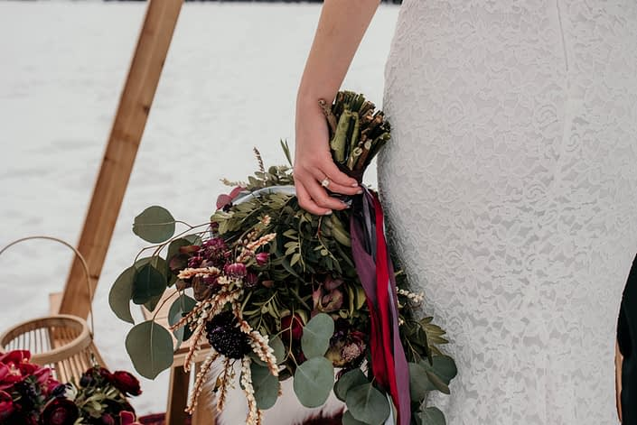 bride with engagement ring holding a loose and natural greenery bouquet tied with trailing silk ribbons