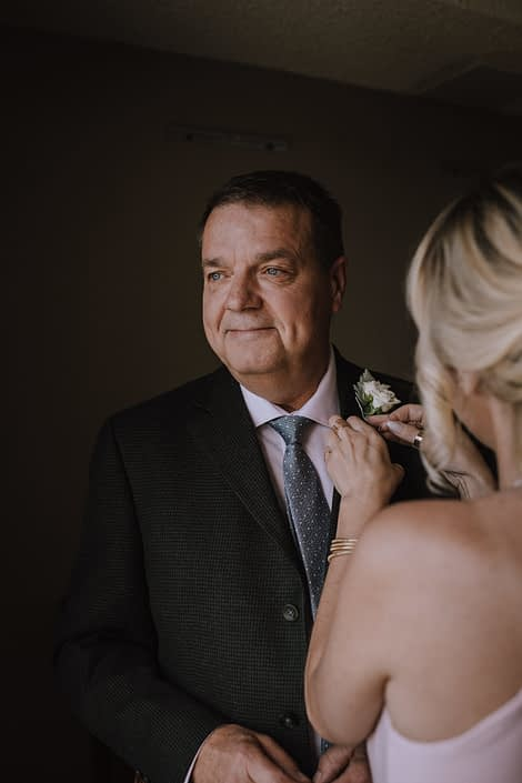 bridesmaid pinning on white rose boutonniere to father