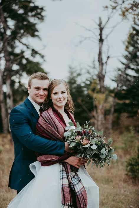 bride and groom photo cheek to cheek with plaid shawl and groom wearing a blue suit bridal bouquet with mixed eucalyptus greenery and red roses and burgundy dahlias and amnesia roses against a natural backdrop in Alberta