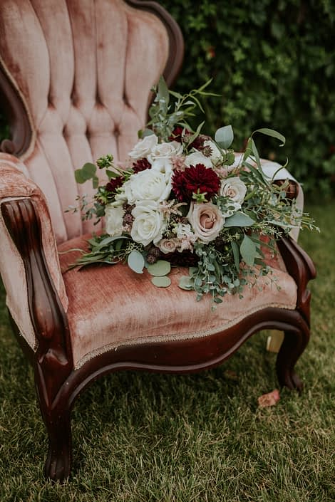 antique blush chair with bridal bouquet of burgundy, blush and ivory and eucalyptus greenery