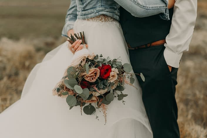 country bride and groom in prairie field with jean jacket on holding a bouquet with red roses and white o'hara garden roses and quicksand roses and eryngium and pink astilbe and eucalyptus