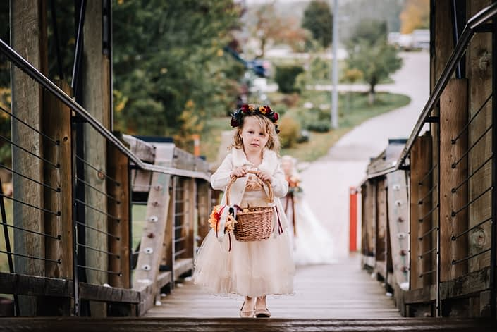 Flowergirl wearing a flowercrown of chrysanthemum, spray roses and eryngium and carrying a basket of autumn colored rose petals